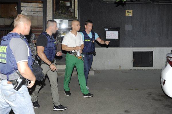 Rendőrök kísérik az elfogott S. Ábelt (fotó: Mihádák Zoltán - MTI)
